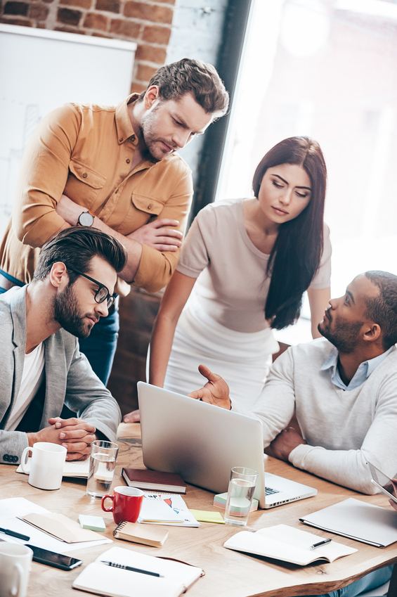 Group of young business people discussing something in office